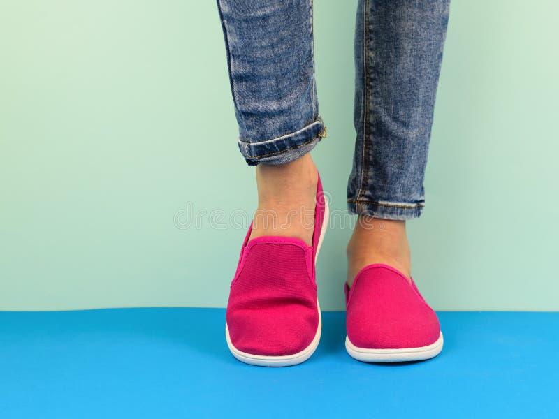 De benen van het Hipstermeisje ` s in jeans op de blauwe vloer door de blauwe muur Moderne hipsterstijl stock fotografie