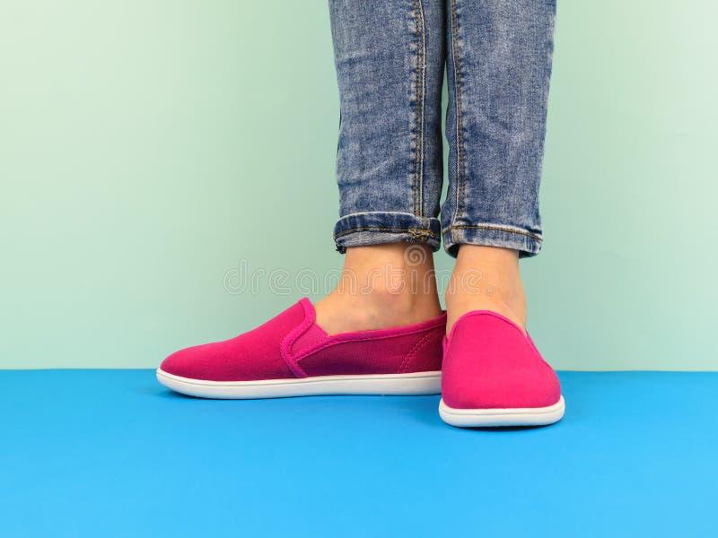 De benen van het Hipstermeisje ` s in jeans op de blauwe vloer door de blauwe muur Moderne stijl stock fotografie