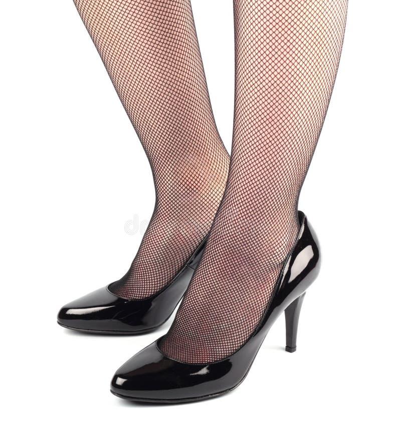 De benen van het meisje in de zwarte schoenen van het octrooileer stock afbeelding