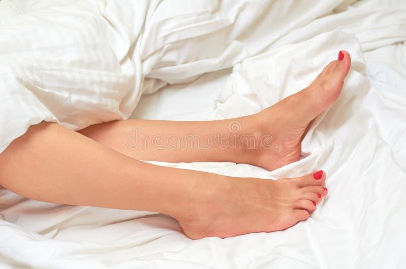 de benen van het meisje liggen op een bed op een witte blad, een rust en een ontspanning stock foto's