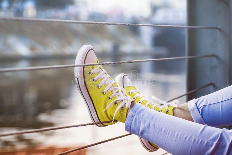 De benen van het meisje in tennisschoenen op de rivierbank Jonge vrouw die jeanstennisschoenen dragen die in een rivierbank zitte stock foto