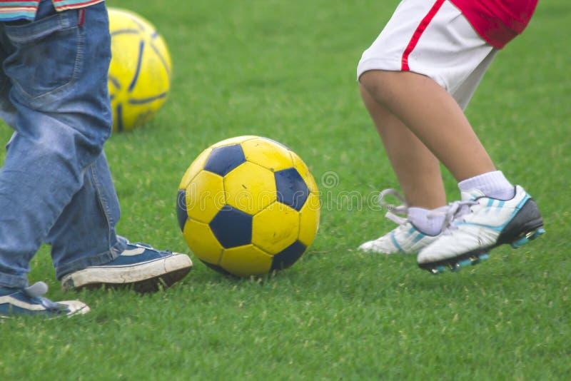 De benen van jonge geitjes schoppen voetbal stock afbeeldingen