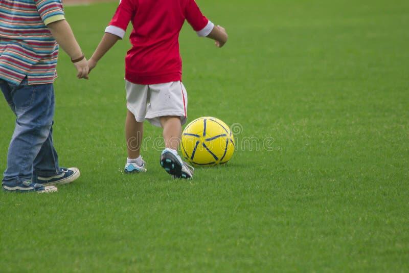 De benen van jonge geitjes schoppen voetbal royalty-vrije stock fotografie