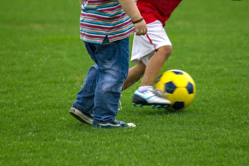 De benen van jonge geitjes schoppen voetbal royalty-vrije stock afbeelding
