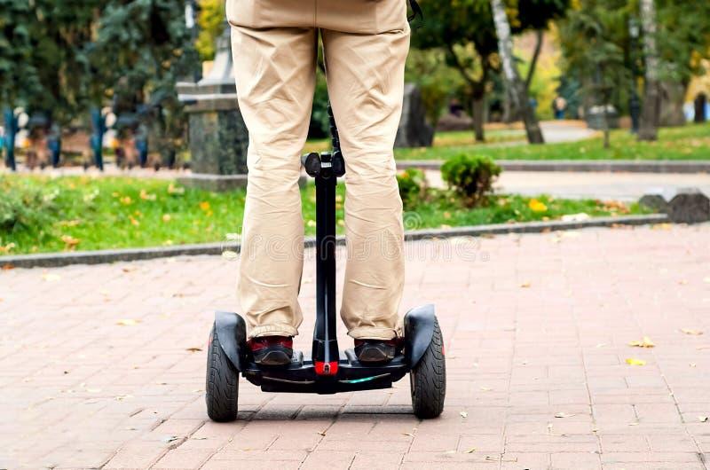 De benen van mensen op gyroscoop met twee wielen tegen de achtergrond van stad parkeren, kopiëren ruimte stock foto's