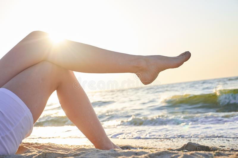 De benen van de mooie vrouw op overzeese achtergrond De zomerdag van Nice royalty-vrije stock foto's