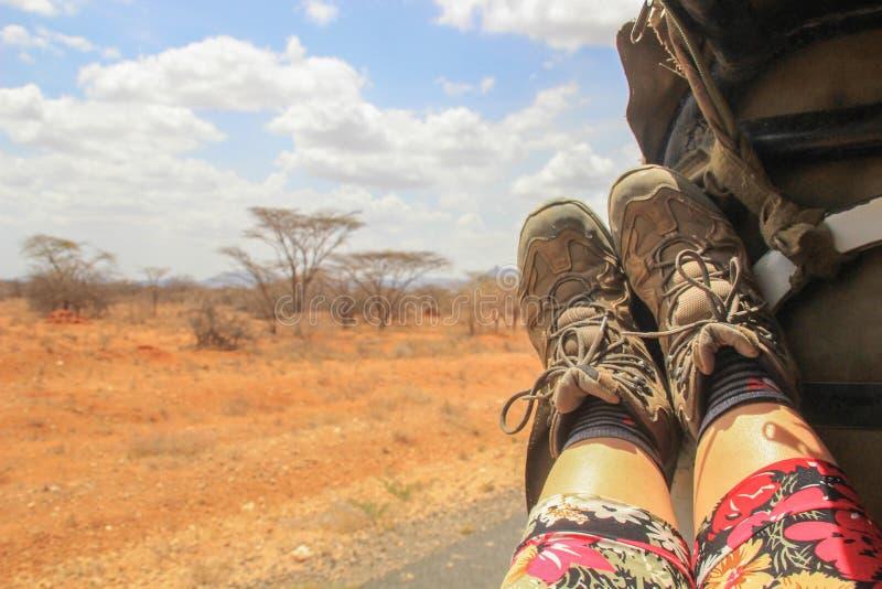 De benen van vrouwen en toeristenlaarzen op de achtergrond van de Afrikaan royalty-vrije stock fotografie