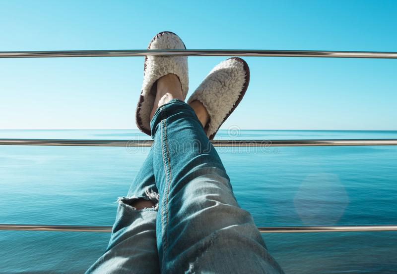 De benen van vrouwen in gescheurde jeans en de witte pantoffels die van het schapenbont op de dwarsbalk van het balkon liggen stock fotografie