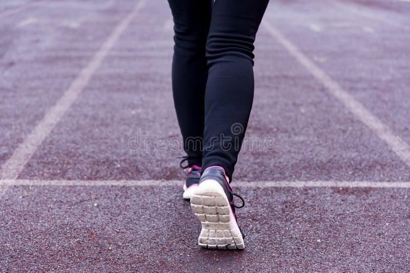 De benen van vrouwen in zwarte sportenbeenkappen en sportenschoenen op een tredmolen van een sporten open stadion stock afbeelding