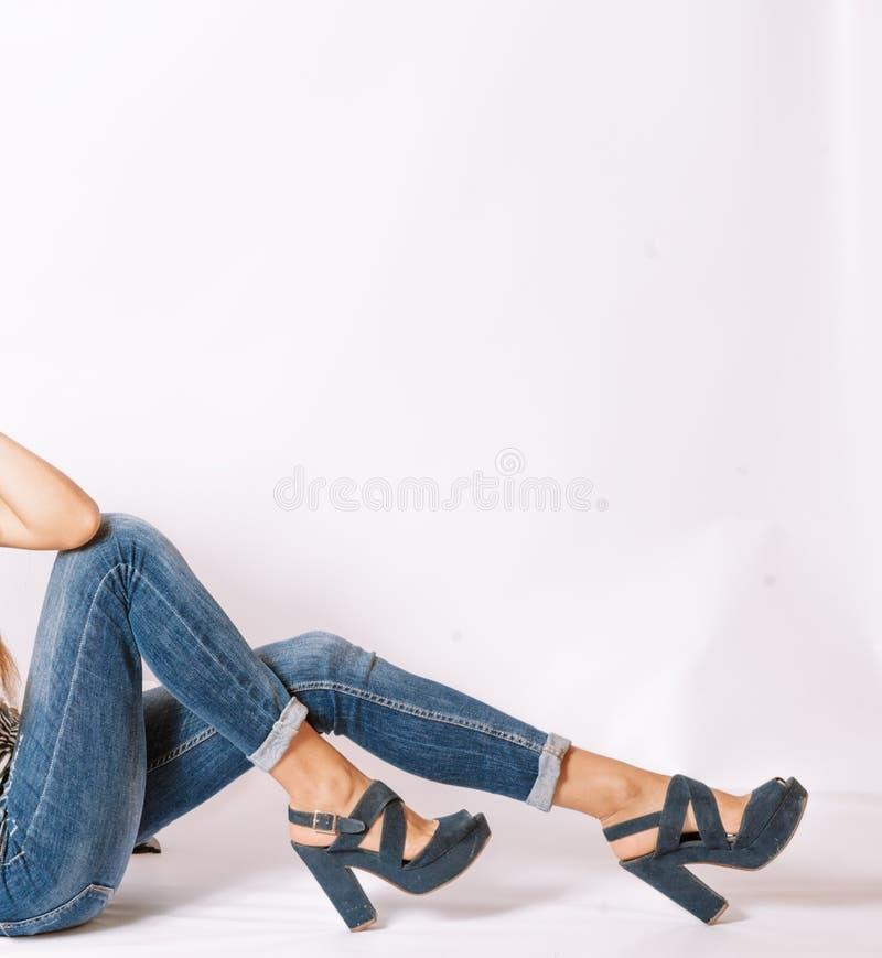 De Benen van de zittingsvrouw in magere jeans op grijs met copyspace royalty-vrije stock foto