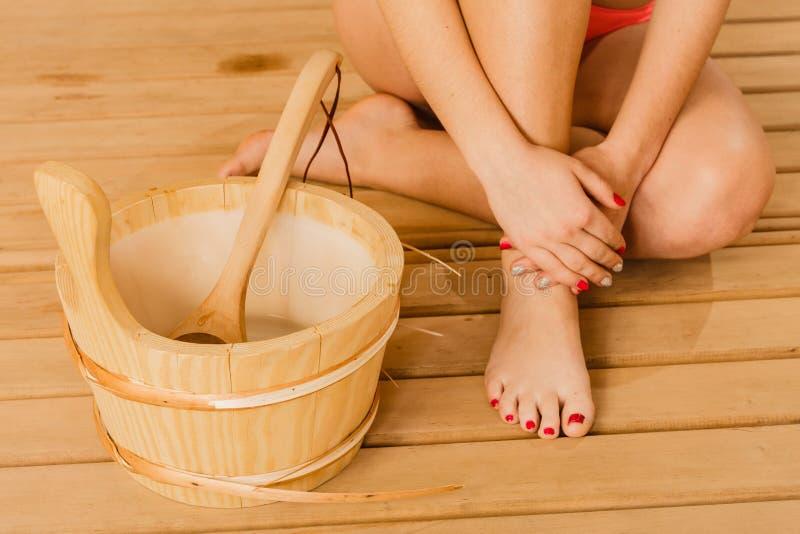 De benenvoeten van de close-up menselijke vrouw en saunaemmer stock foto