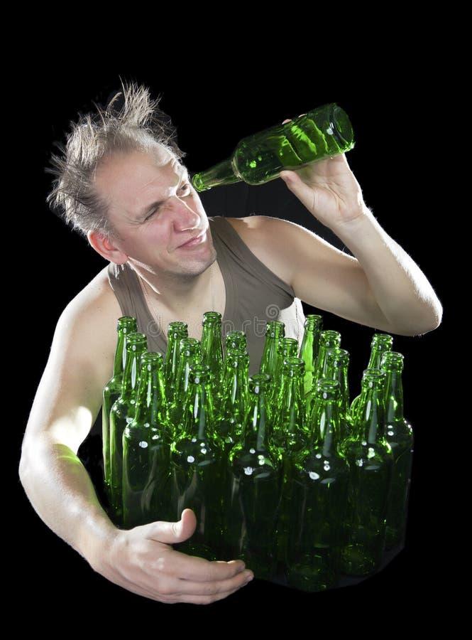 De benevelde mens wil de laatste drank van bier van een lege fles drinken stock fotografie