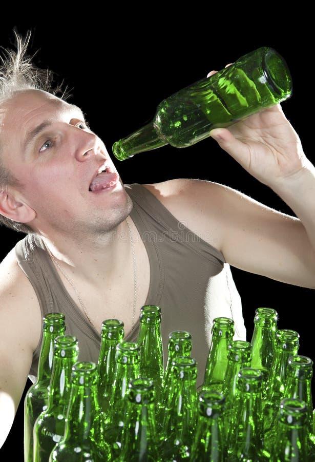 De benevelde mens wil de laatste drank van bier van een lege fles drinken stock afbeeldingen