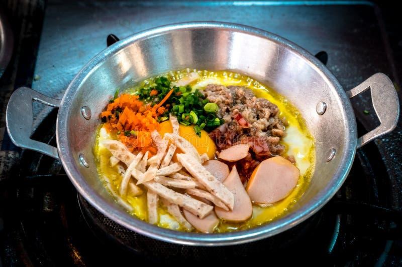 De berömd panorerade äggen för frukosten thai mat är toppning för stekt ägg med korven, grönsaken och bacon i den varma pannan royaltyfria foton