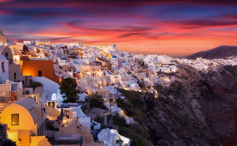De berömda röda sommarsolnedgångarna över den grekiska ön av Santorini arkivbilder