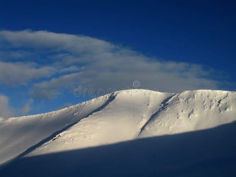 De berg en de wolken van de sneeuw stock foto's