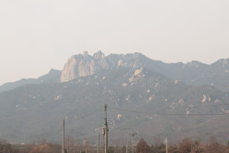 De berg kijkt vage toe te schrijven aan dichte fijne stofluchtvervuiling in Seoel royalty-vrije stock afbeeldingen