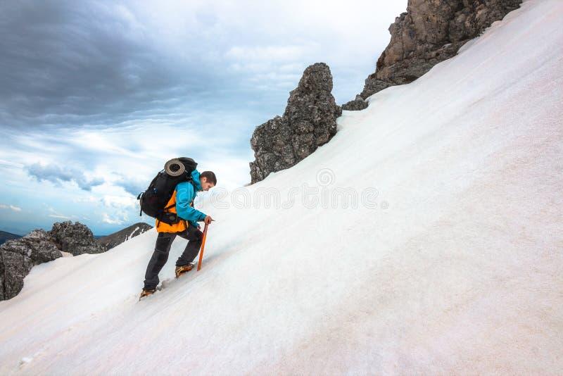 De bergbeklimmer in steil sneeuwde helling stock afbeelding