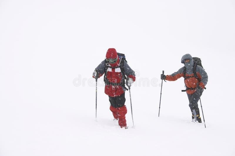 De bergbeklimmers op de slechte winter doorstaan stock afbeelding