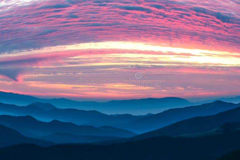 De bergen bekijken vele gestapeld mistig gamma en purpere Wolken royalty-vrije stock fotografie
