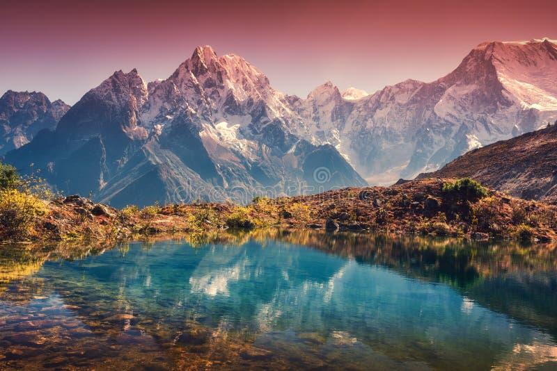 De bergen met sneeuw behandelden pieken, rode die hemel in meer wordt weerspiegeld stock fotografie