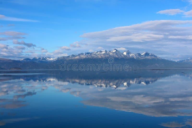 De bergen met sneeuw worden weerspiegeld in het water onder blauwe hemel royalty-vrije stock afbeelding