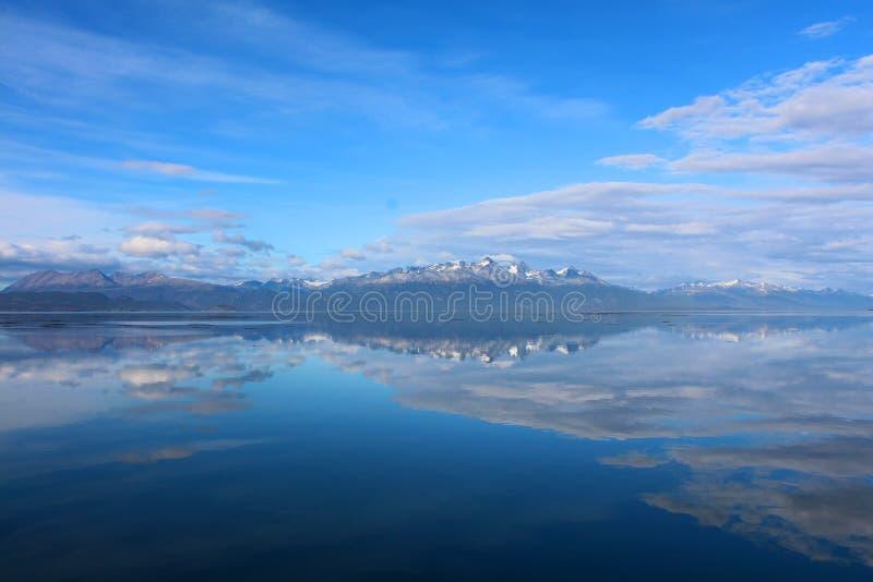 De bergen met sneeuw worden weerspiegeld in het water onder blauwe hemel royalty-vrije stock foto's