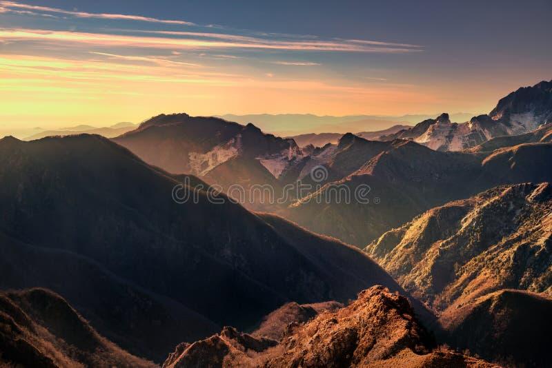 De bergen van Alpiapuane en marmeren steengroevemening bij zonsondergang Carrara stock foto