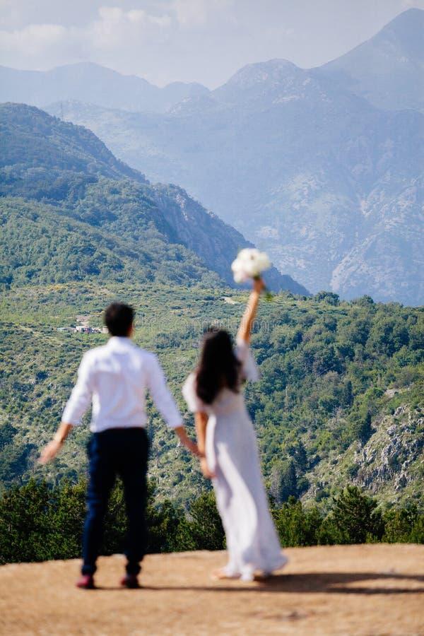 De bergen van de het paarreis van het wittebroodswekenhuwelijk steunen mening stock foto