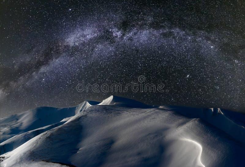 De bergen van de nachtwinter in Maanlicht en Melkweg in hemel stock foto's