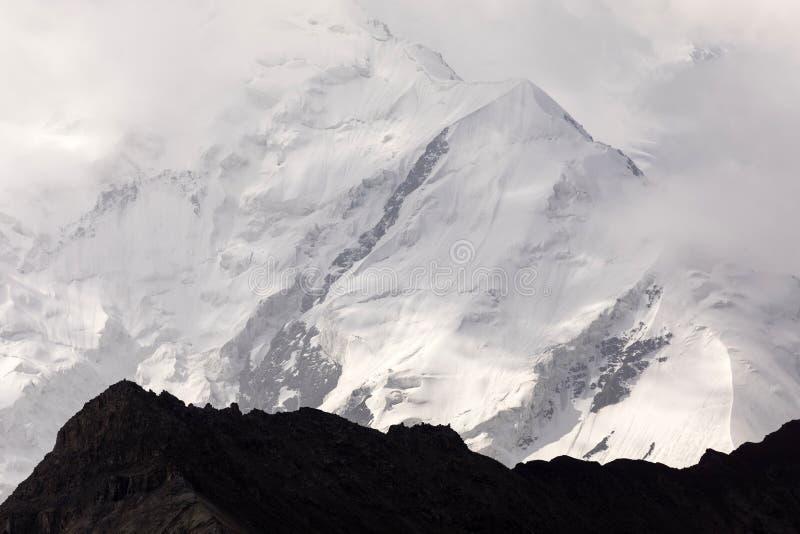 De bergen van Pamir met pieklenin, wat door wolken, Kyrgyzstan wordt gehuld royalty-vrije stock foto's