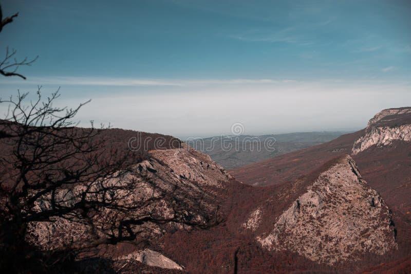 De berglandschap van de herfst Nationale reserve Karadag Rode bos en blauwe hemel stock afbeeldingen