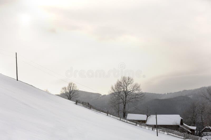 De berglandschap van de winter Sneeuwhelling, houten omheining en huis op bosrijke bergrand en de heldere blauwe ruimteachtergron royalty-vrije stock foto's