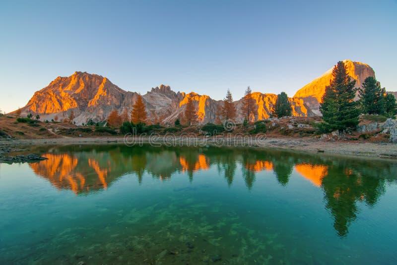 De bergrotsen en de de herfstbomen dachten in water van Limides-Meer bij zonsondergang, Dolomietalpen, Italië na stock foto's