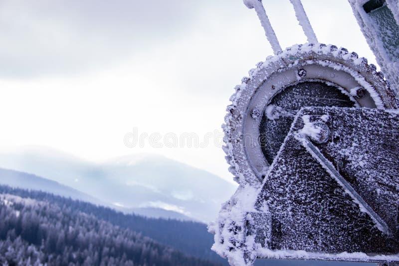 De bergtoevlucht is een snow-covered toestel van een boomlift, de bergen en een steil-gekleurde sombere hemel op de achtergrond royalty-vrije stock afbeelding
