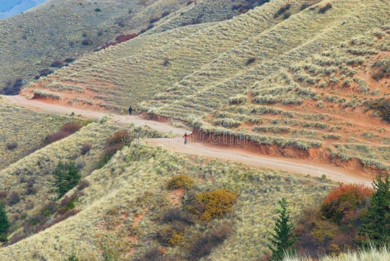 De bergvallei van de herfst en kleine fietsers stock fotografie