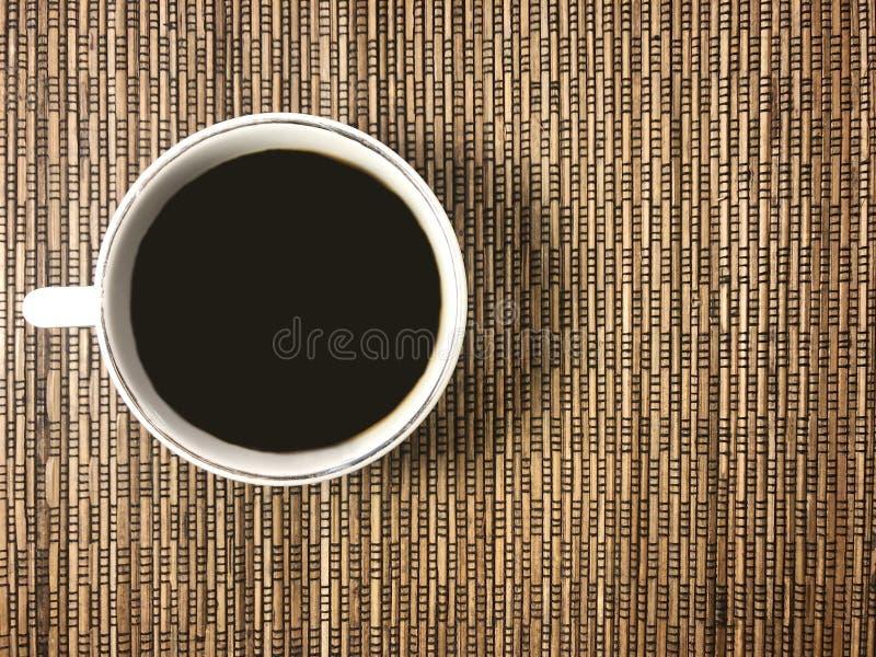 De berichtraad met een kop van koffie op de rieten achtergrond stock foto