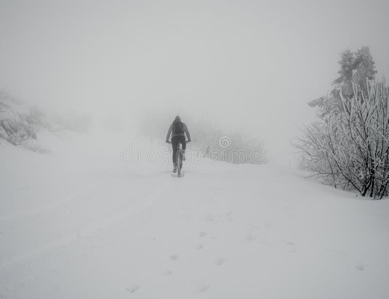 De berijdende fiets van de bergfietser op de sneeuwsleep royalty-vrije stock afbeeldingen
