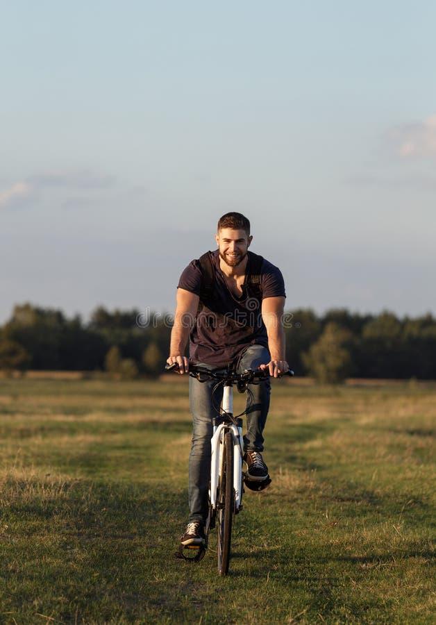 De berijdende fiets van de jonge mensenfietser in hout bij zonsondergang royalty-vrije stock afbeelding