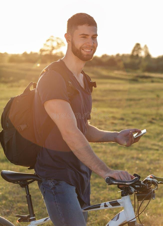 De berijdende fiets van de jonge mensenfietser in hout bij zonsondergang stock fotografie