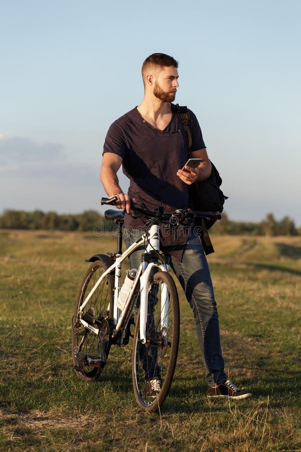 De berijdende fiets van de jonge mensenfietser in hout bij zonsondergang royalty-vrije stock fotografie