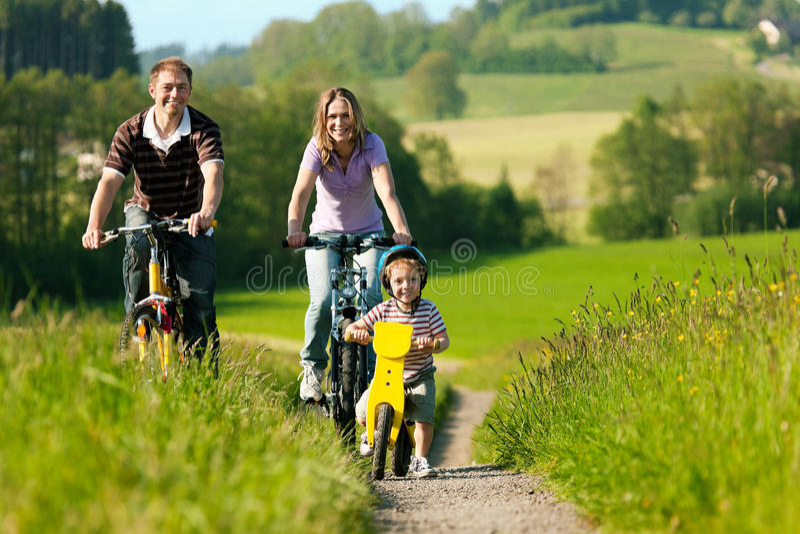 De berijdende fietsen van de familie in de zomer stock afbeeldingen