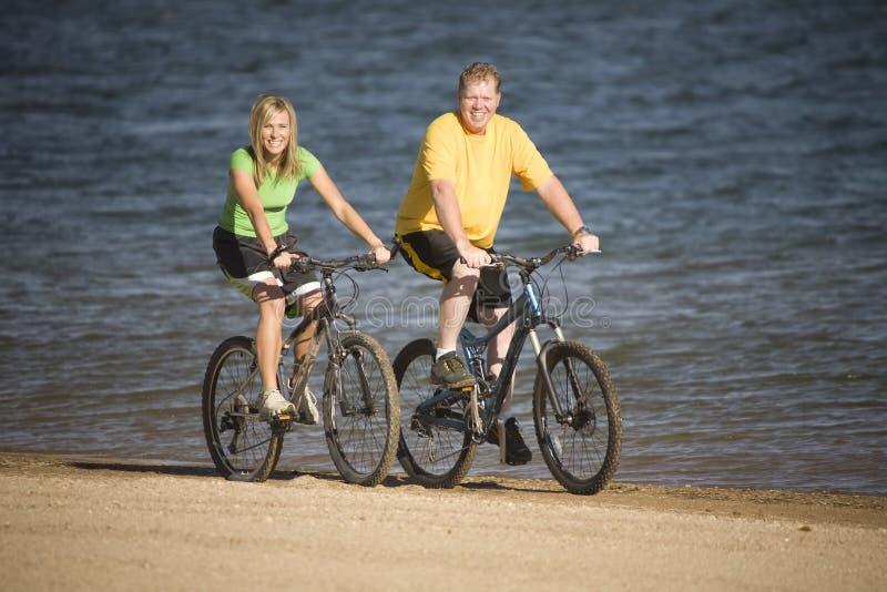 De berijdende fietsen van de man en van de vrouw stock foto's