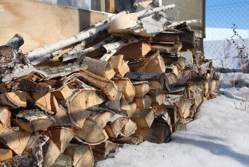 De berkehoutlogboeken zich stapelden in een stapel in de sneeuw op die op het ontsteken voor de winter in een stapel wordt voorbe stock afbeeldingen