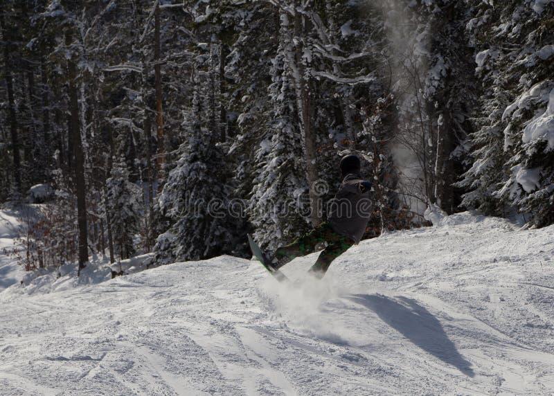 De berm van de Snowboarderklap met stijl Opheffende raad op bovenkant terwijl het slepen van staart op sneeuw stock foto's