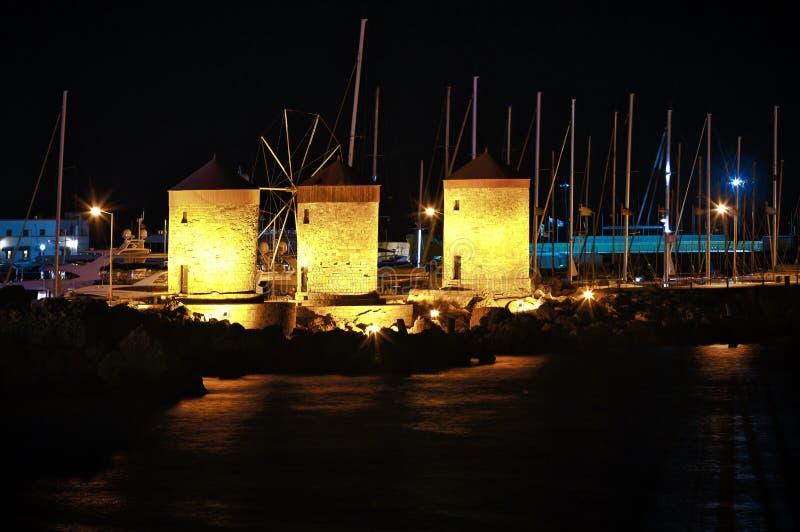 De beroemde molens van het Eiland Rhodos op pijler onder de voorraden van jachten bij nacht met mooie verlichting stock foto