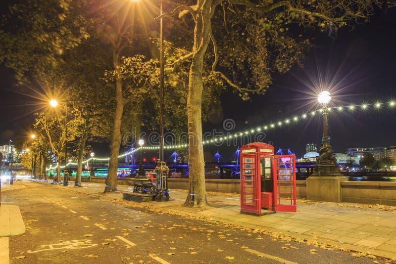 De beroemde rode telefooncel rond nacht stock foto
