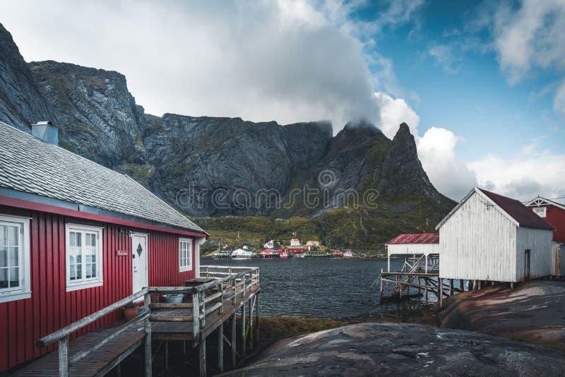 De beroemde toeristische attractie van Reine in Lofoten, Noorwegen met rode rorbu huisvest, wolken, regenachtige dag met brug en  royalty-vrije stock afbeelding