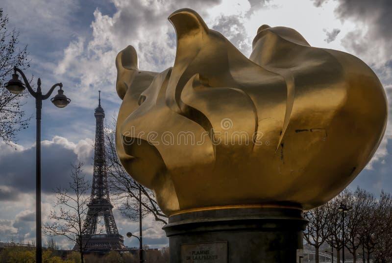 De beroemde vlam van vrijheid met de Toren van Eiffel in de achtergrond en een dramatische hemel, Parijs, Frankrijk stock afbeeldingen