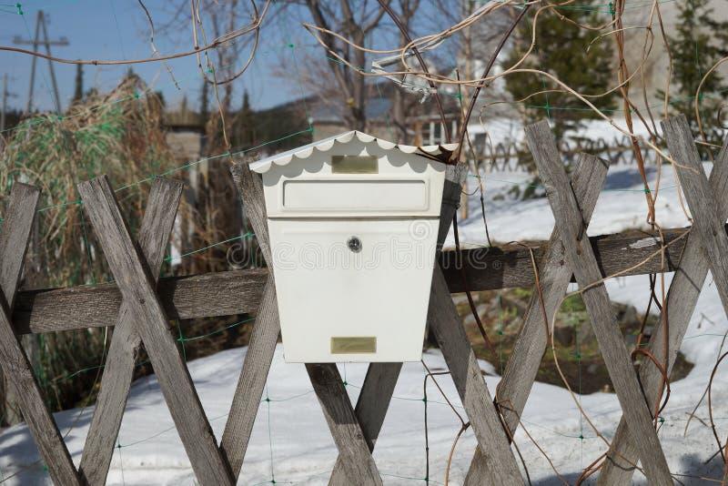 De beschadigde brievenbus, in de vorm van een huis, hangt op een houten omheining in de lente royalty-vrije stock afbeelding